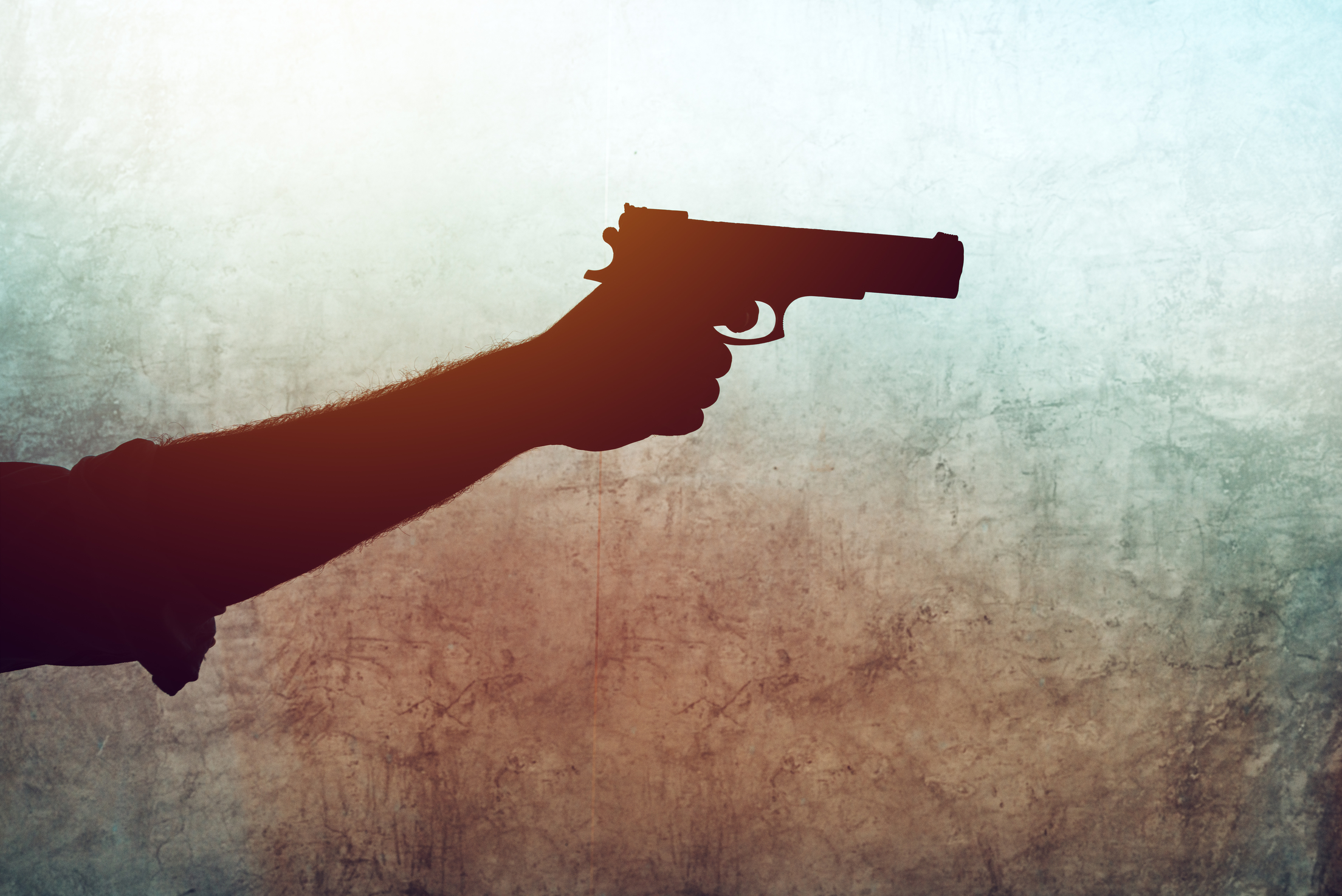 Hand with a gun on grunge background. Violence and crime with use of fire weapon.