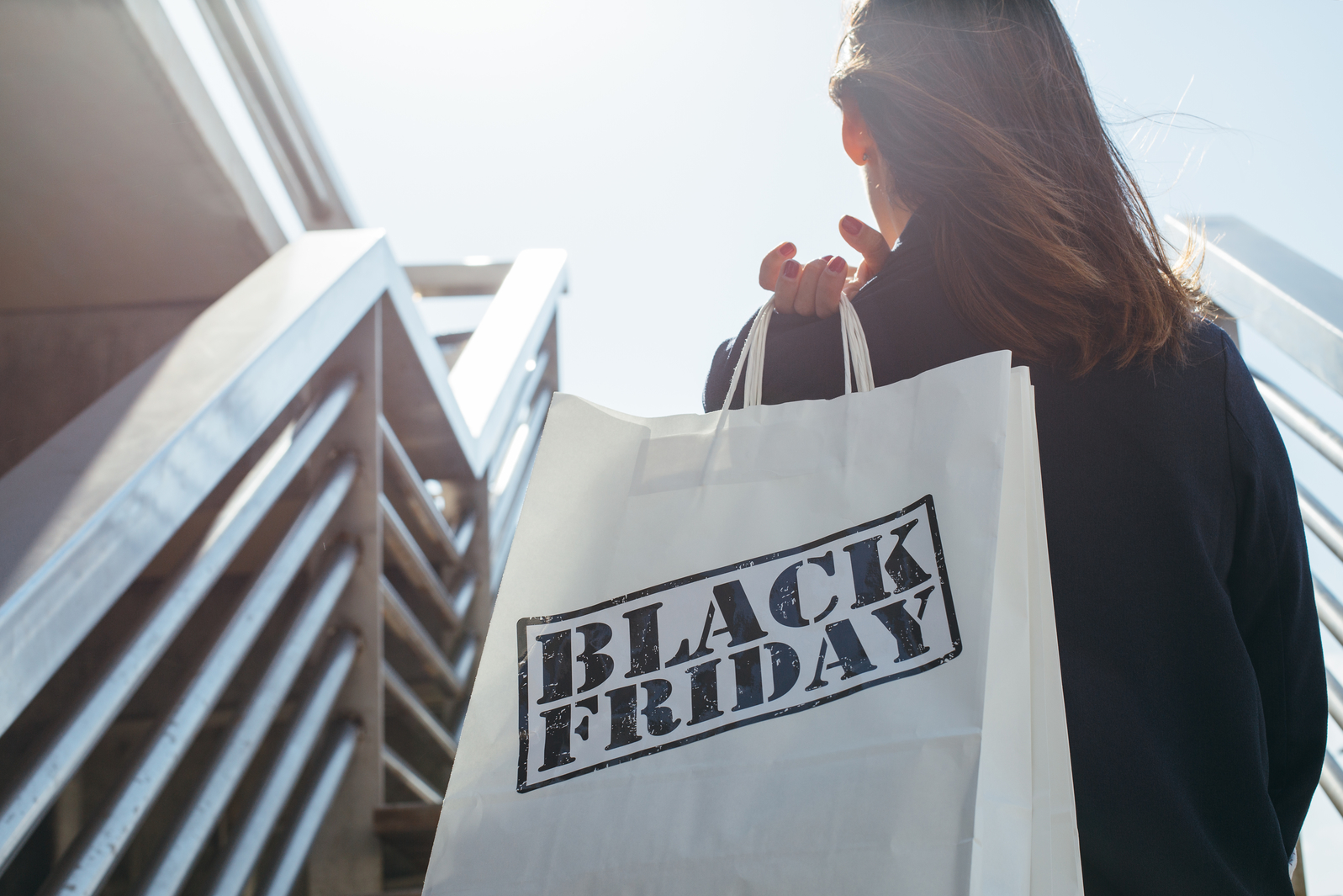Rear view of incognito brunette holding Black Friday shopping bag while standing outdoors. Copyspace