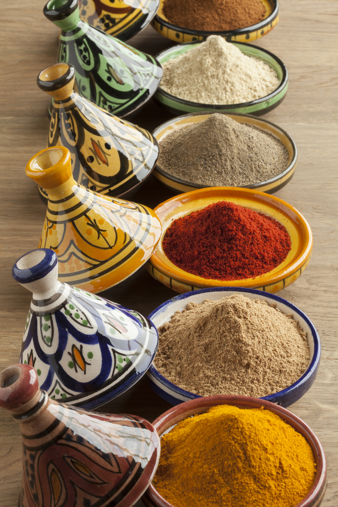 Diversity of Moroccan powder herbs in colorful ceramic tagines