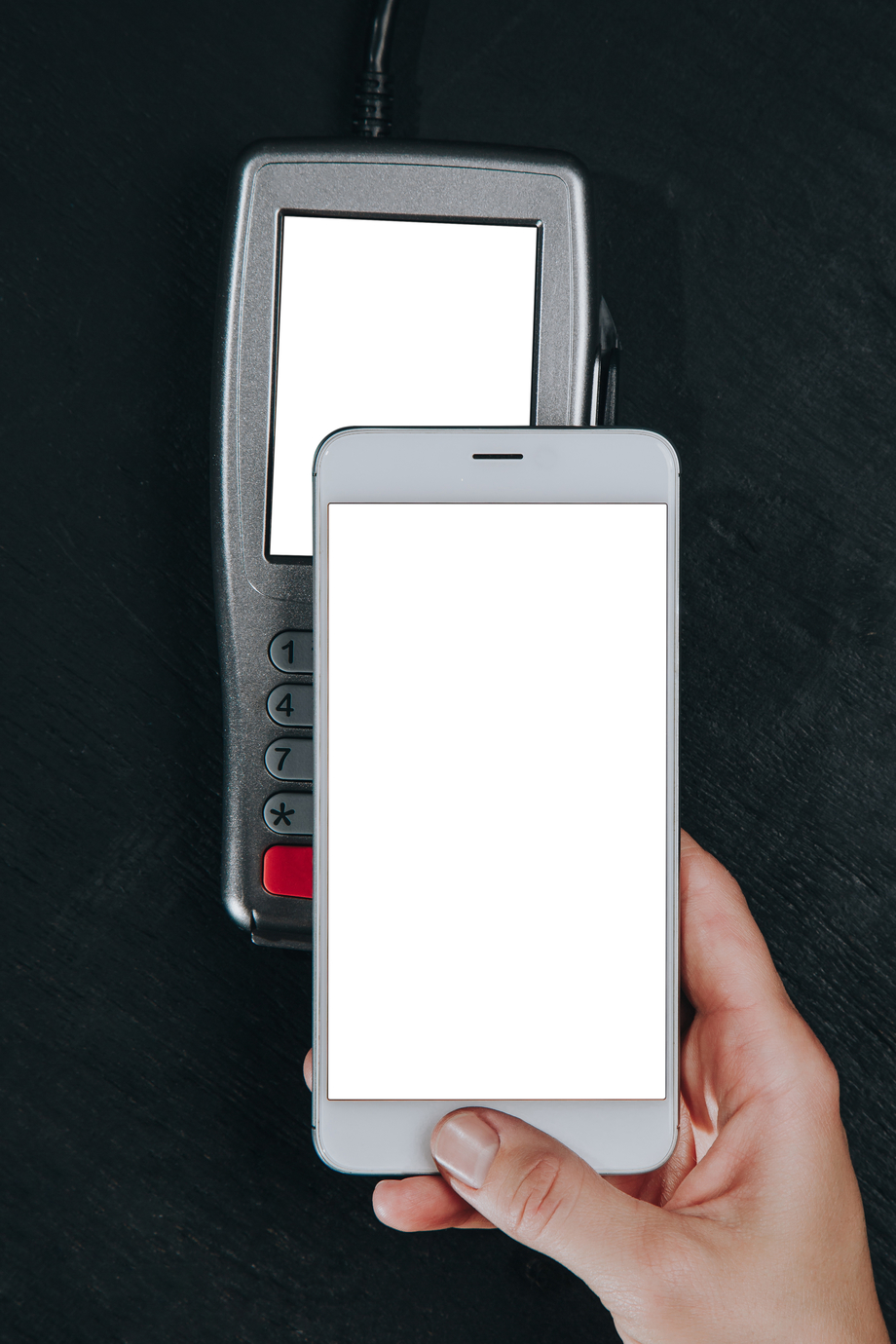 Top view of person using contactless payment with smartphone. Clear white mockup screen template of phone and pos terminal on dark wooden desk